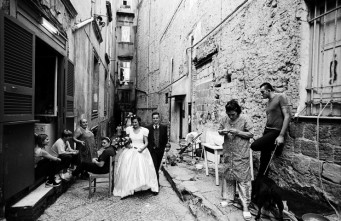 Anewly married couple walking throught the narrow street of Naples.