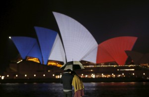 A couple stands in the rain as the blue, white and red colours of France's national flag are projected onto the sails of Sydney's Opera House in Australia
