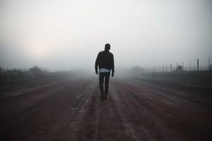 uomo-che-cammina-su-strada-deserta