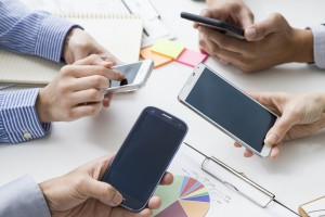 Four people each have a cell phone in the office
