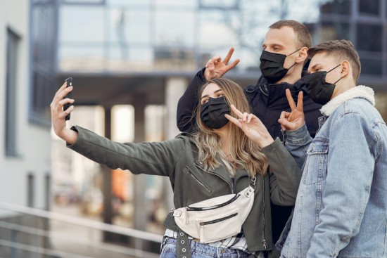 friends-taking-selfie-on-smartphone-on-street-during-covid-3985187